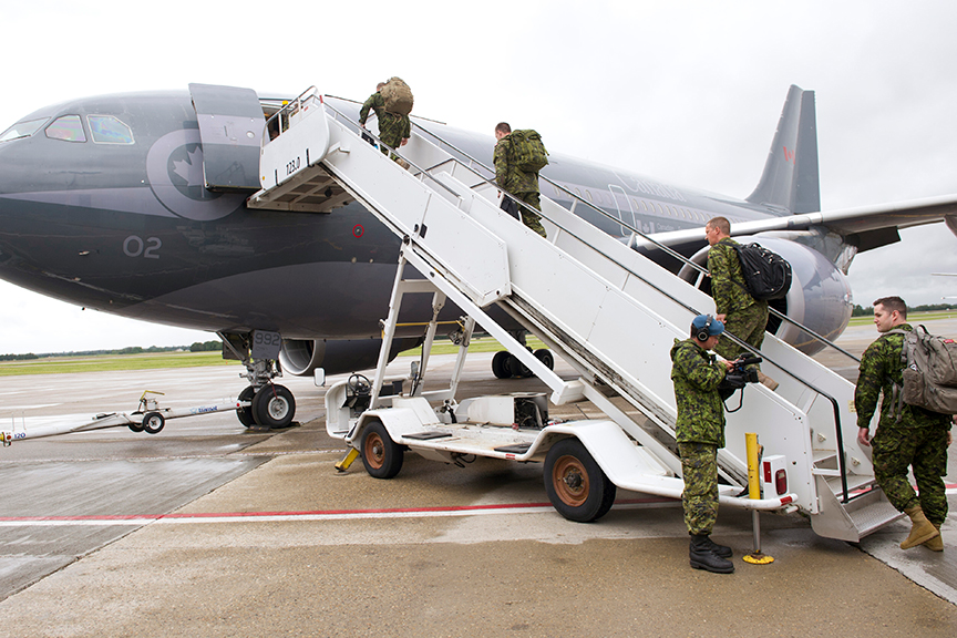 Des soldats du 1er Groupe-brigade mécanisé du Canada qui se déploient sur l'opération REASSURANCE embarquent un avion CT-150 Polaris à l'aéroport international d'Edmonton le 9 juin 2017.