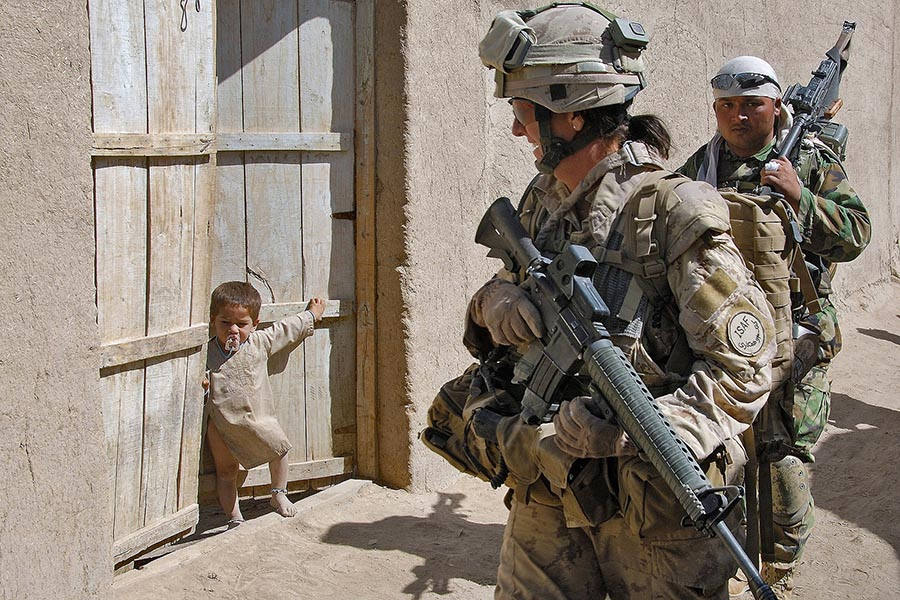 Master Corporal Kelly Harding smiles at an Afghan boy during a patrol in the compound village of Nakhonay in October, 2008.